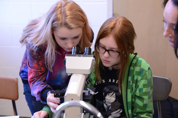STEM attendees at microscope